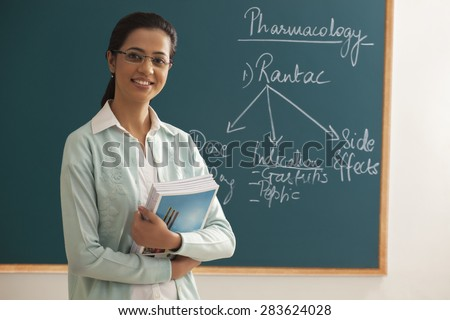 Portrait of young female teacher holding books against green board - stock photo