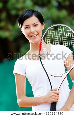 Portrait of young female tennis player with racket at the tennis court