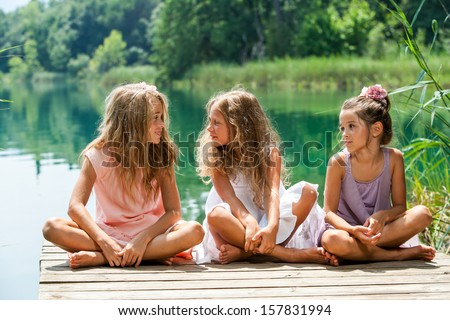 Portrait of young female threesome having conversation on river jetty. - stock photo