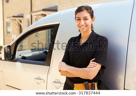 Portrait of young female trade worker standing by a van - stock photo