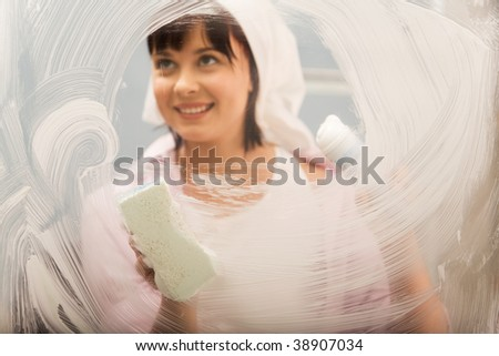 Portrait of young female washing window and smiling