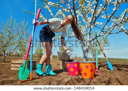 Portrait of young female with rakes and spade on garden  - stock photo