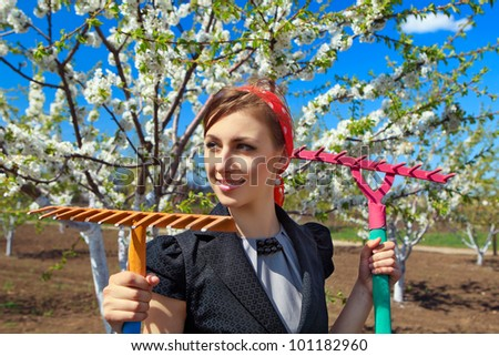 Portrait of young female with rakes on garden - stock photo