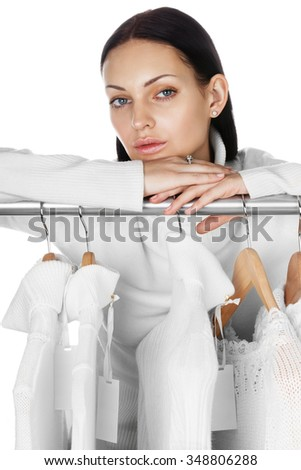 Portrait of young female with selection of winter clothes. Sale season concept. - stock photo
