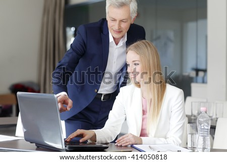Portrait of young financial assistant working on laptop while senior professional man standing next to her and giving investment advise.
