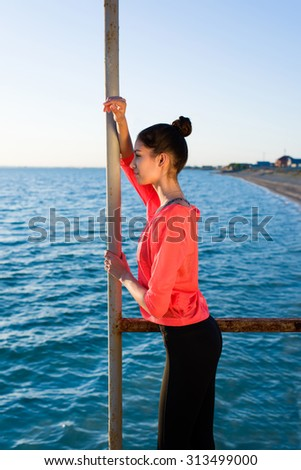 Portrait of young fit woman standing on the pier enjoying sea view while relax after a morning run on the beach, female jogger taking break after active workout exercise in sunny summer day outdoors - stock photo