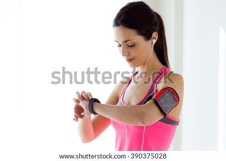Portrait of young fitness woman looking at her smart watch while taking a break.