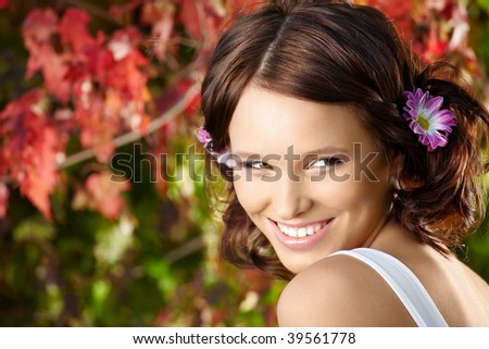 Portrait of young flirting woman against red leaves in a summer garden - stock photo