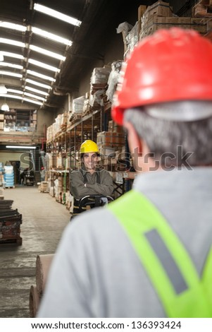 Portrait of young foreman with arms crossed standing at warehouse - stock photo