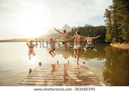 Portrait of young friends jumping into the water from a jetty. Young people having fun at the lake on a summer day. - stock photo