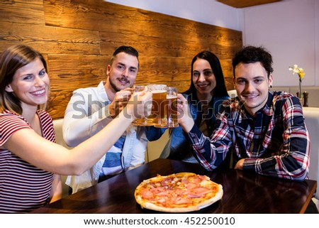 Portrait of young friends smiling while toasting beer at bar - stock photo