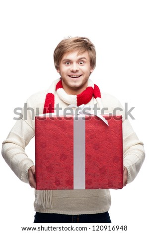 portrait of young funny cheerful caucasian man which holding big red christmas gift with funny expression - stock photo
