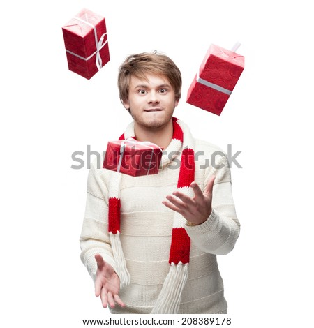 portrait of young funny cheerful caucasian man which juggle red christmas gifts with funny expression - stock photo