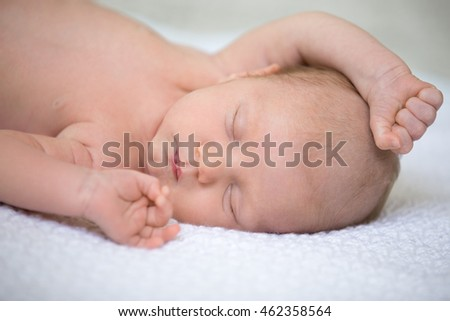 Portrait of young funny newborn babe napping on soft white knitted blanket with his arms up. Cute caucasian new born child sleeping. Healthy one month old kid lying on bed with closed eyes. Close-up