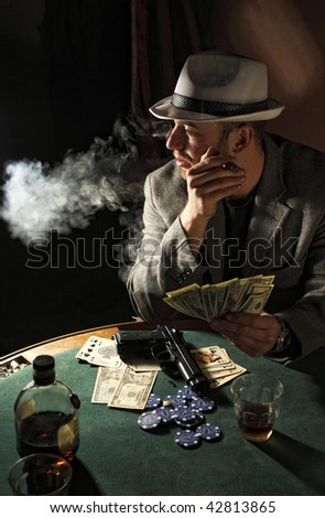 portrait of young gangster smoking and play poker - stock photo