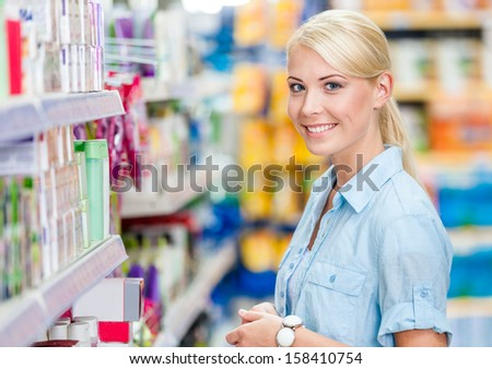 Portrait of young girl at the market standing near the shelves with cosmetics - stock photo