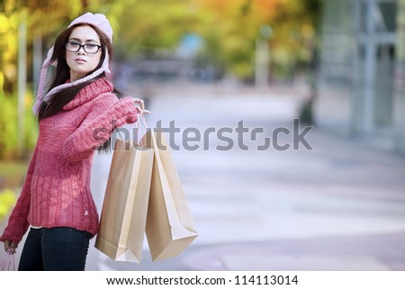 Portrait of young girl carrying shopping bag and dressed for winter time with hat on her head.