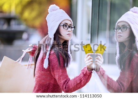 Portrait of young girl carrying shopping bag and holding a card. shot outdoor with reflection on the glass - stock photo