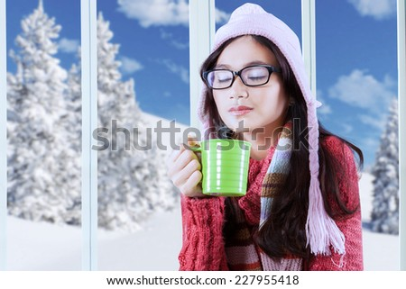 Portrait of young girl closed eyes while enjoy hot coffee at home in winter day - stock photo