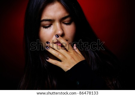 Portrait of young girl crying in the dark - stock photo
