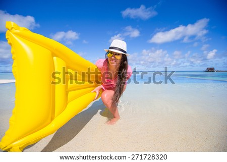 Portrait of young girl having fun with air mattress in swimming pool