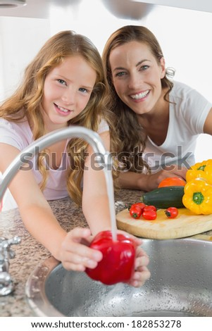 Portrait of young girl helping her mother to wash vegetables in the kitchen at home