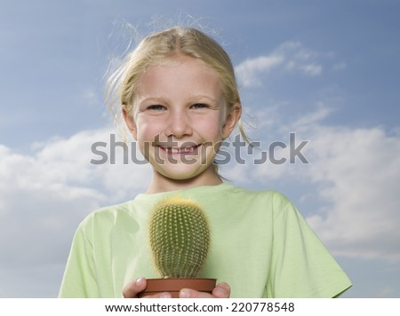 Portrait of young girl holding a spiny cactus against a blue sky to illustrate environmental issues - stock photo