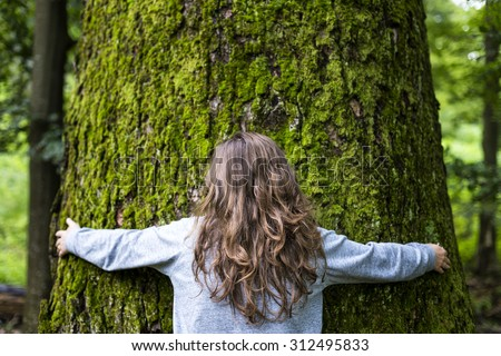 Portrait of young girl hugging a big tree in the forest