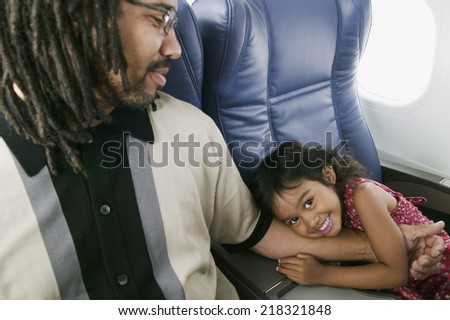 Portrait of young girl hugging father's arm - stock photo