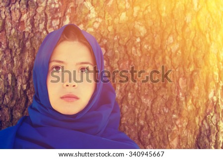 Portrait of young girl in a blue shawl, tree trunk background