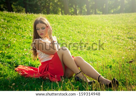 Portrait of young girl in a red skirt in park