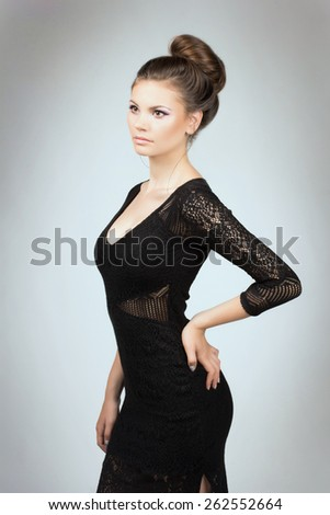 Portrait of young girl in black dress. Portrait of beautiful brunette woman in black dress. - stock photo