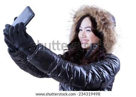 Portrait of young girl in black jacket taking self picture with a smartphone, isolated on white - stock photo