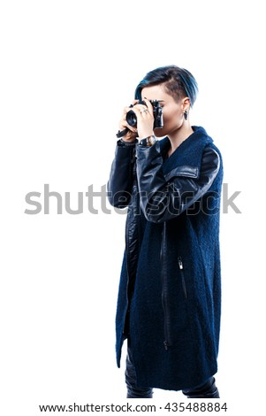 Portrait of young girl in coat with hairstyle photographing with old film camera. Studio shot
