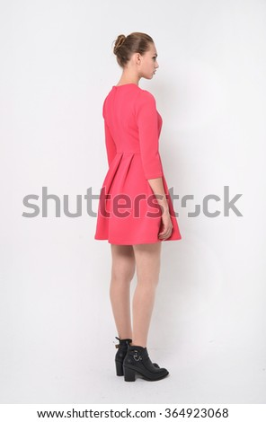 Portrait of young girl in red dress back in studio - stock photo