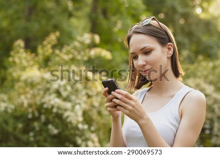 Portrait of young girl in sunglasses dialing the number