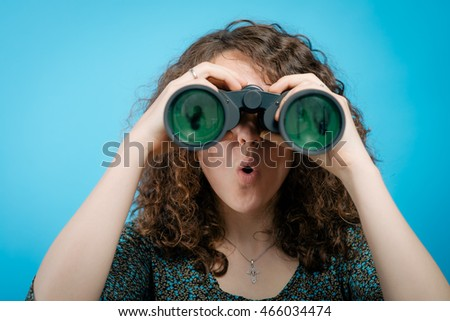 portrait of young girl looking through a binoculars