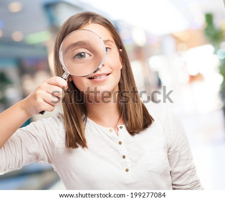 portrait of young girl looking through a magnifying glass - stock photo