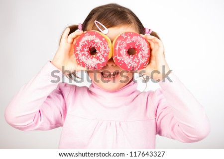 Portrait of young girl looking through two pink donuts, white background,