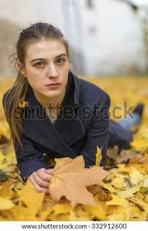 Portrait of young girl lying in fallen leaves. - stock photo
