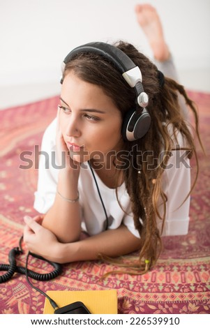 Portrait of young girl lying on the floor and listening to the music - stock photo
