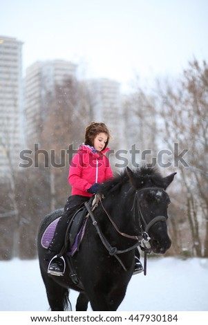 Portrait of young girl on a black horse at the winter equestrian site in front of trees and buildings - stock photo