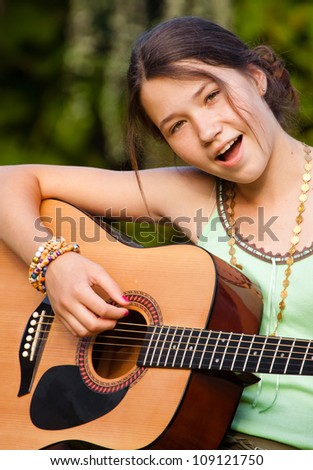 Portrait of young girl playing the guitar and singing in nature - stock photo