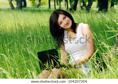 Portrait of young girl sitting with notebook near the tree