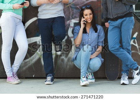 Portrait of young girl talking on the phone while her friends typing on their smart phones - stock photo