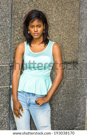 Portrait of Young Girl. Wearing a green tank top, fashionable jeans, drop earrings, a young pretty black woman is standing against the wall, sad, lost in thought. - stock photo