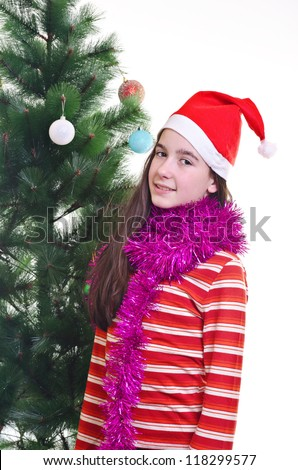 portrait of young girl wearing beanie, standing near christmas tree, eye contact, vertical shot