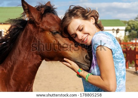 portrait of young girl with a foal on the farm - stock photo
