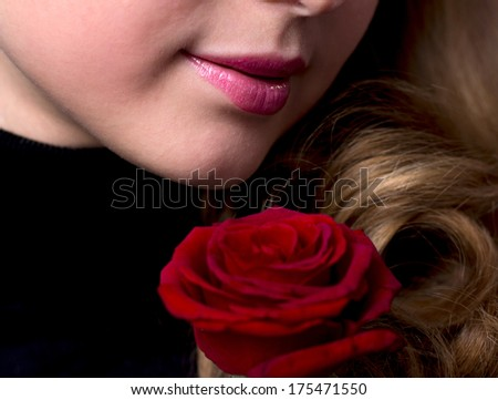 portrait of young girl with a red rose near her lips