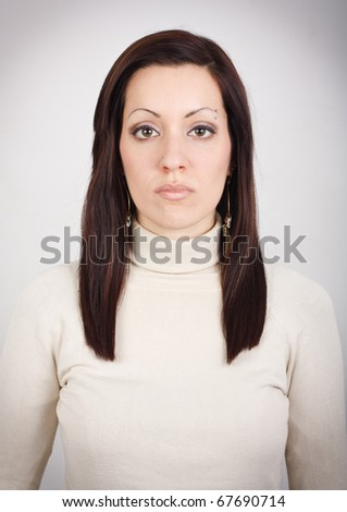 Portrait of young girl with blank expression, looking at camera. - stock photo